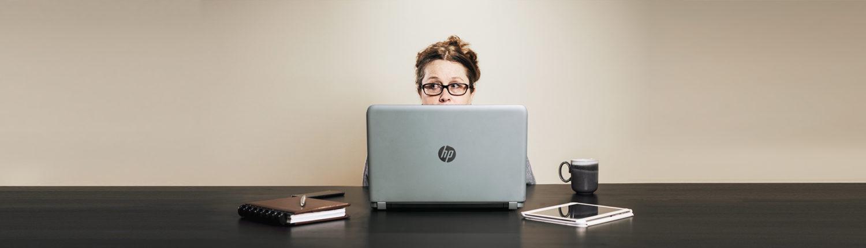 Amanda Claesens looking over the top of her laptop